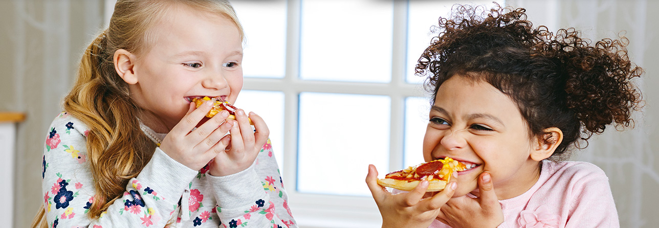 2 girls smiling and eating food